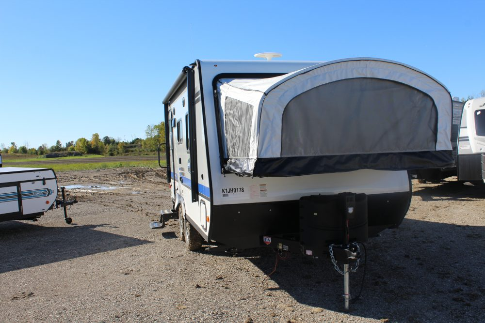 Front and Right exterior sides of the Jayco Jay Feather X19H, with its 13' Power awning with LED lights , and its 2 20 lb. propane bottles with auto regulator.