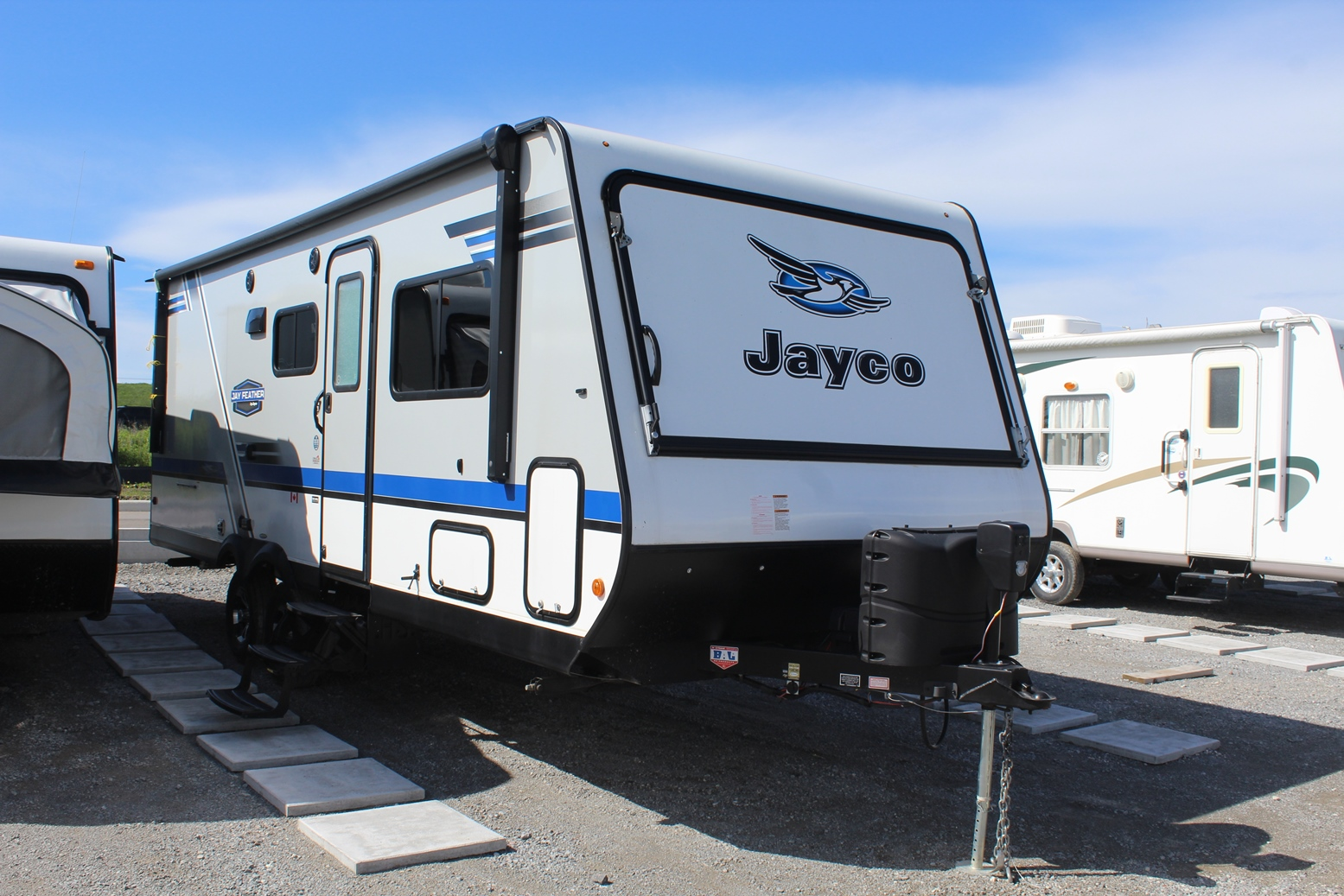 Exterior View of the Jayco Jay Feather X23E Hybrid Trailer with its 19' Awning and Aluminum-tread entry steps.