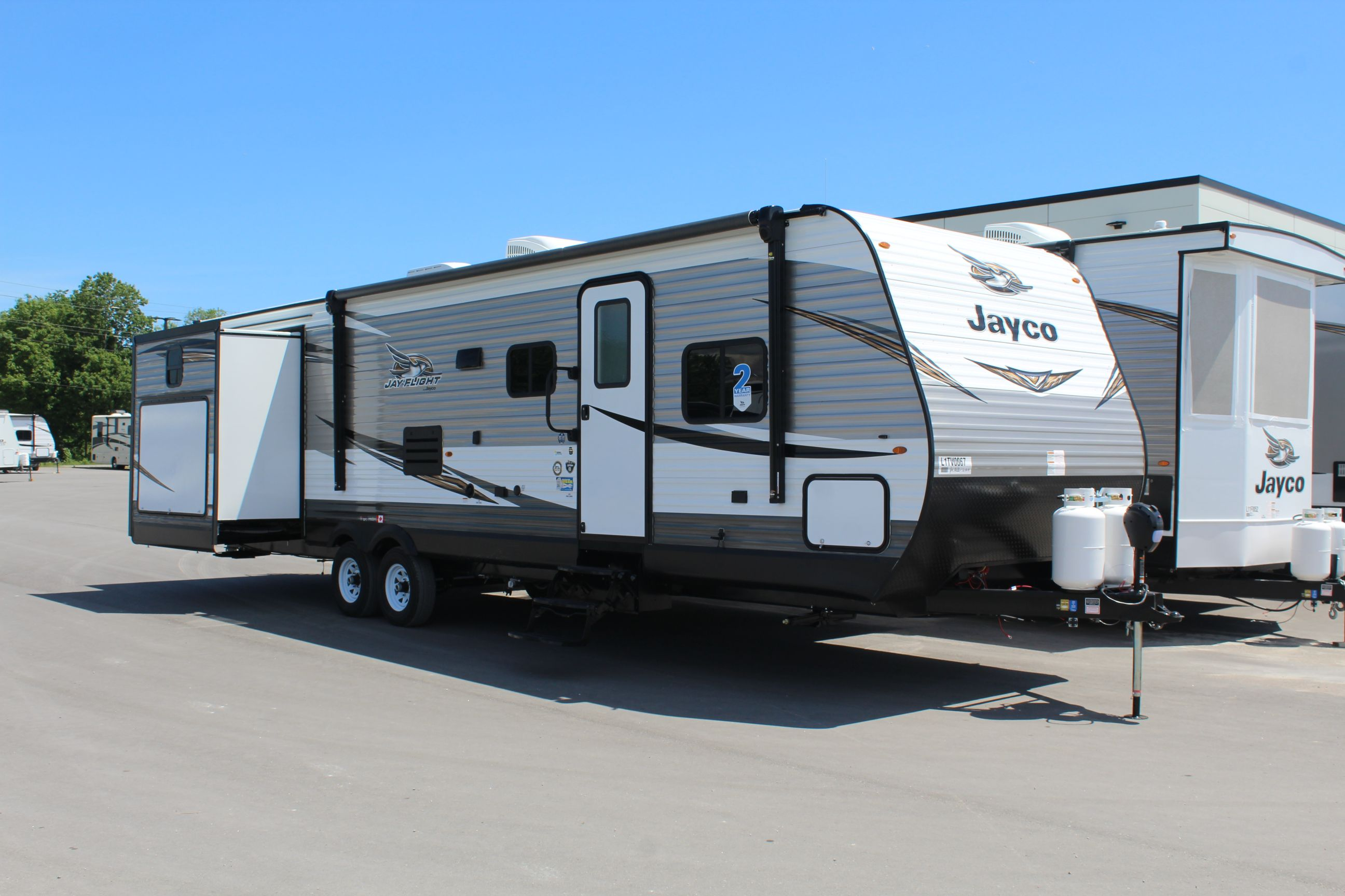 Front and right Exterior sides of the Jayco Jay Flight 32TSBH, with its 18' Power awning with speakers and LED lights, and Outside Kitchen with 2 burner cook-top, sink and small refrigerator.