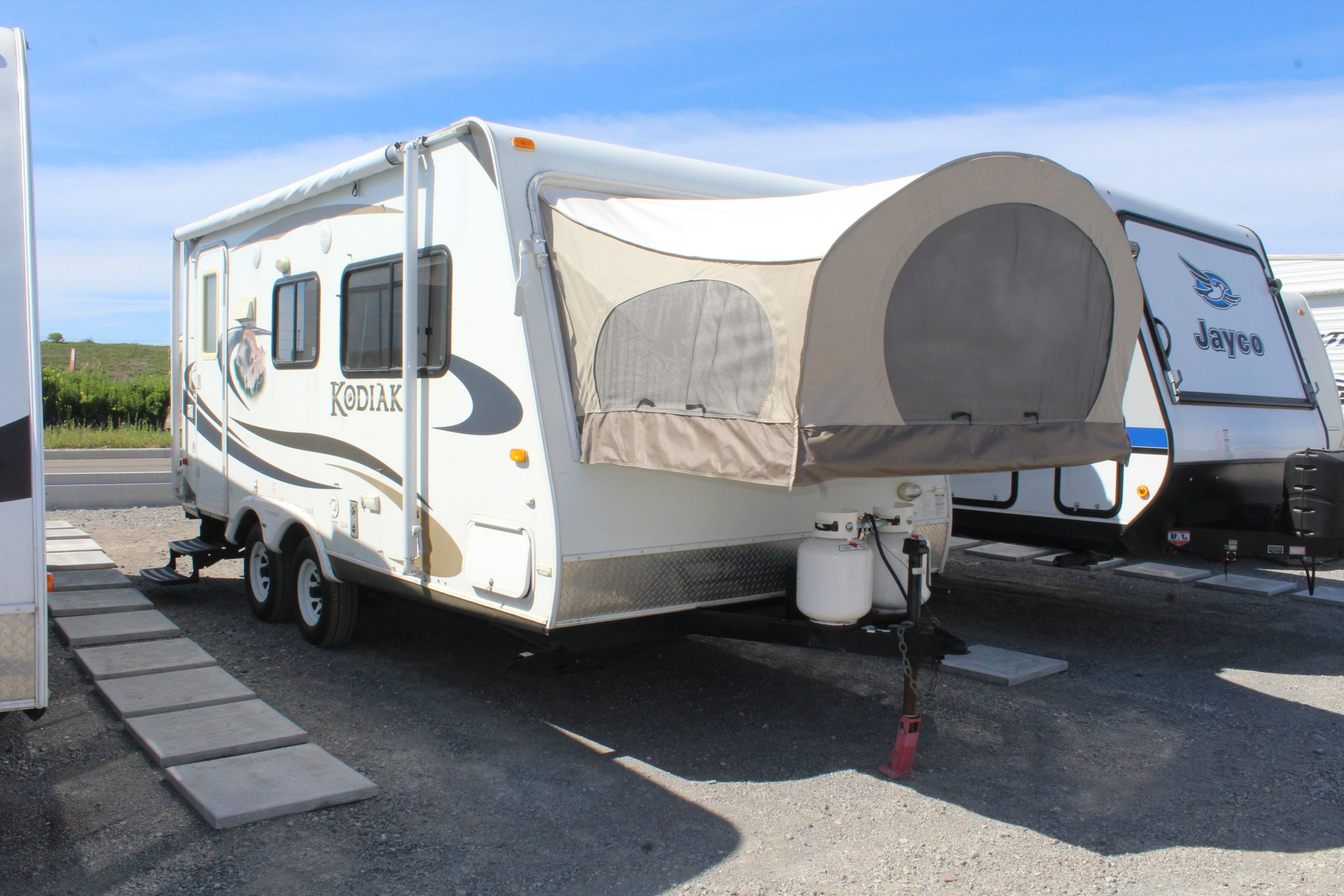 Front and Right side of the Dutchman Kodiak 184, with its Rear entry, two 40 lb Propane Tanks, and Awning.