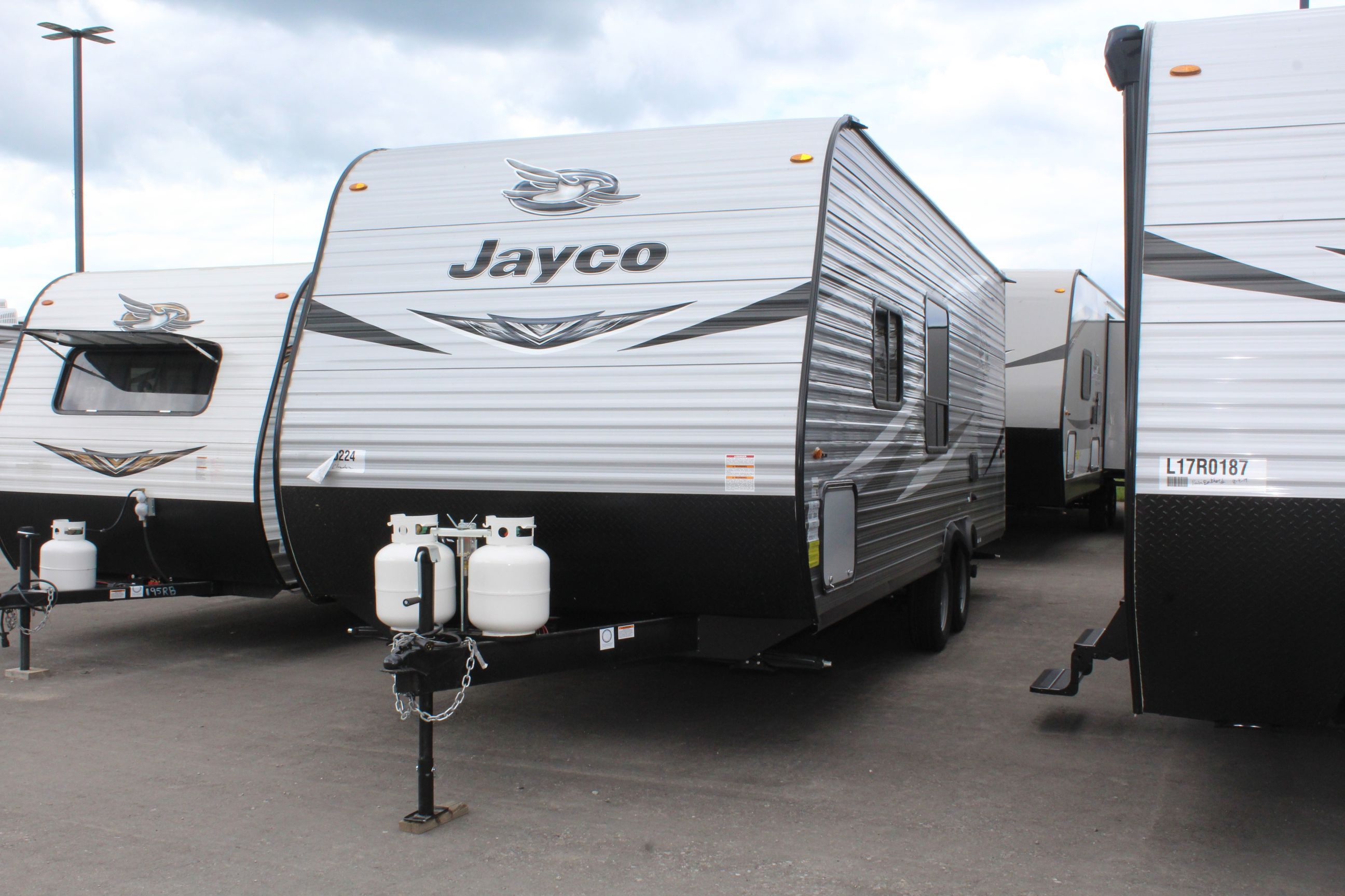 Front and Left exterior sides of the Jayco Jay Flight SLX 224BH, with its 13' Power awning with LED lights & speakers, and Keyed-Alike™ entry and baggage doors.
