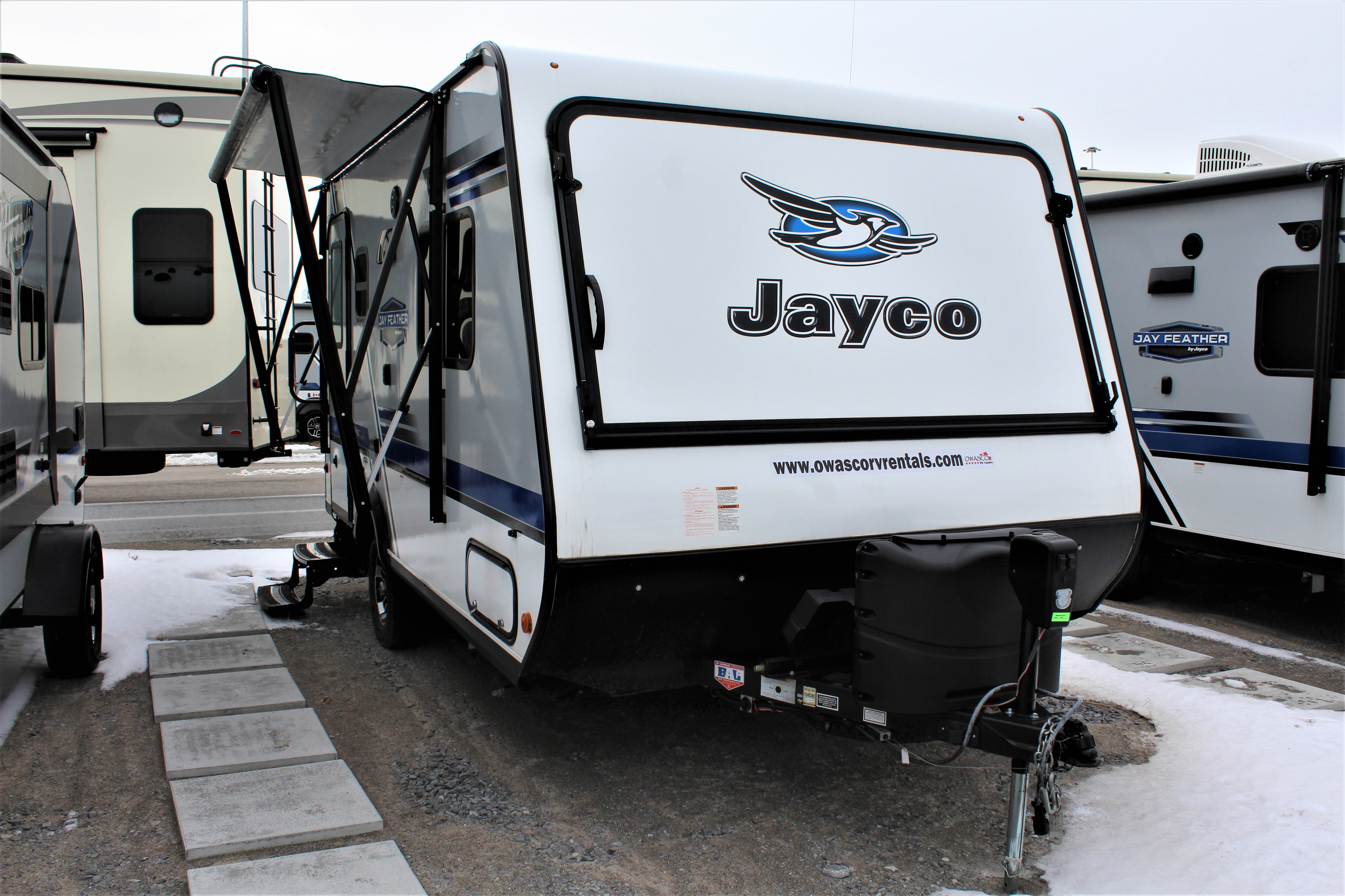 Front and right Exterior sides of the Jayco Jay Feather X17Z, with its 10' Power awning with LED lights, and Folding assist handle on main entry doors, and its 2 20-pound propane bottles with auto regulator.