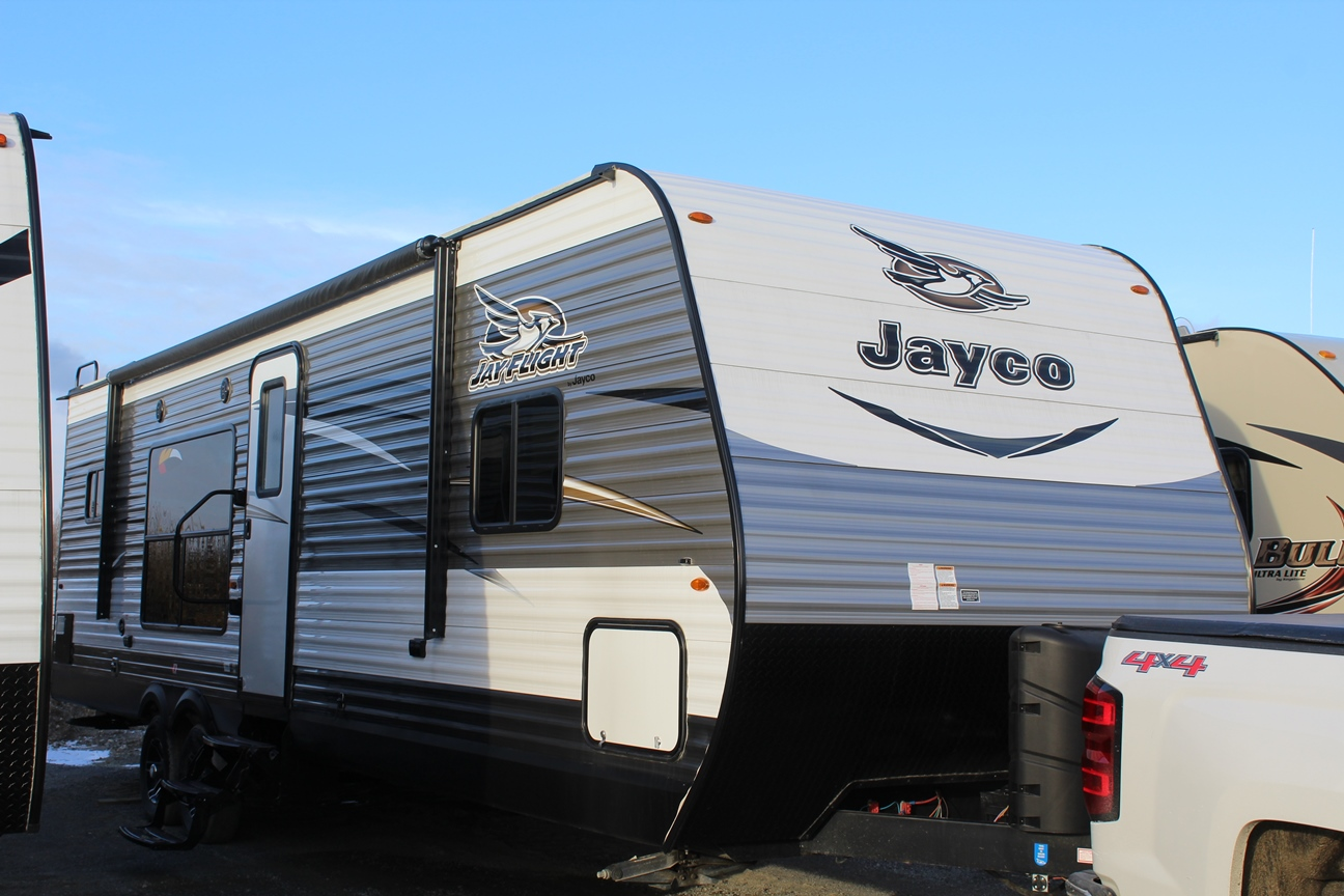 Front and Right exterior sides of the Jayco Jay Flight 29RKS, with its 18' Power awning with speakers and LED lights, Large main entry door grab handle, and MORryde® StepAbove™ Entry Steps.