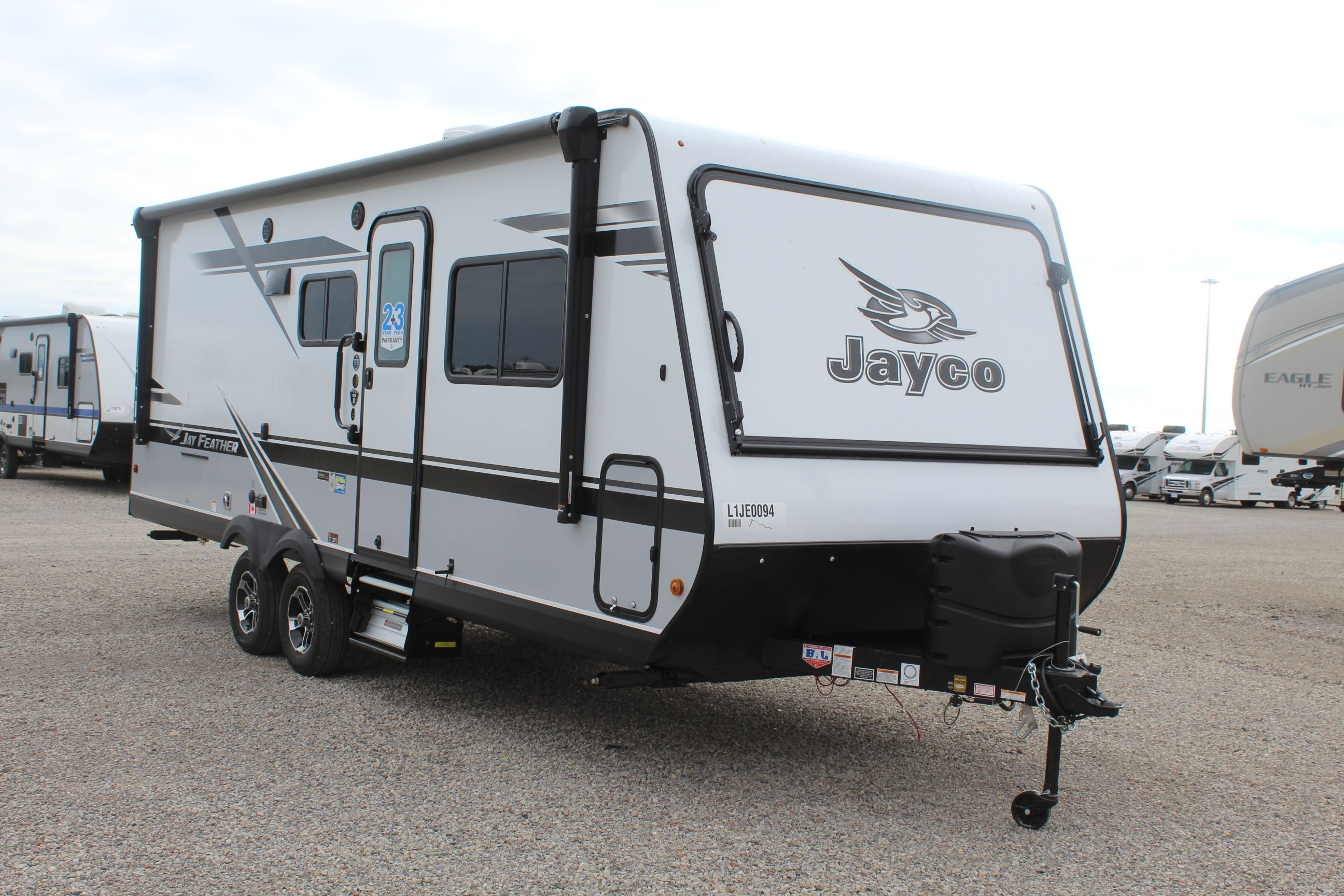 Front and Right Exterior View of the Jayco Jay Feather X23E Hybrid Trailer with its 19' Power Awning with LED lighting throughout and Aluminum-tread entry steps.
