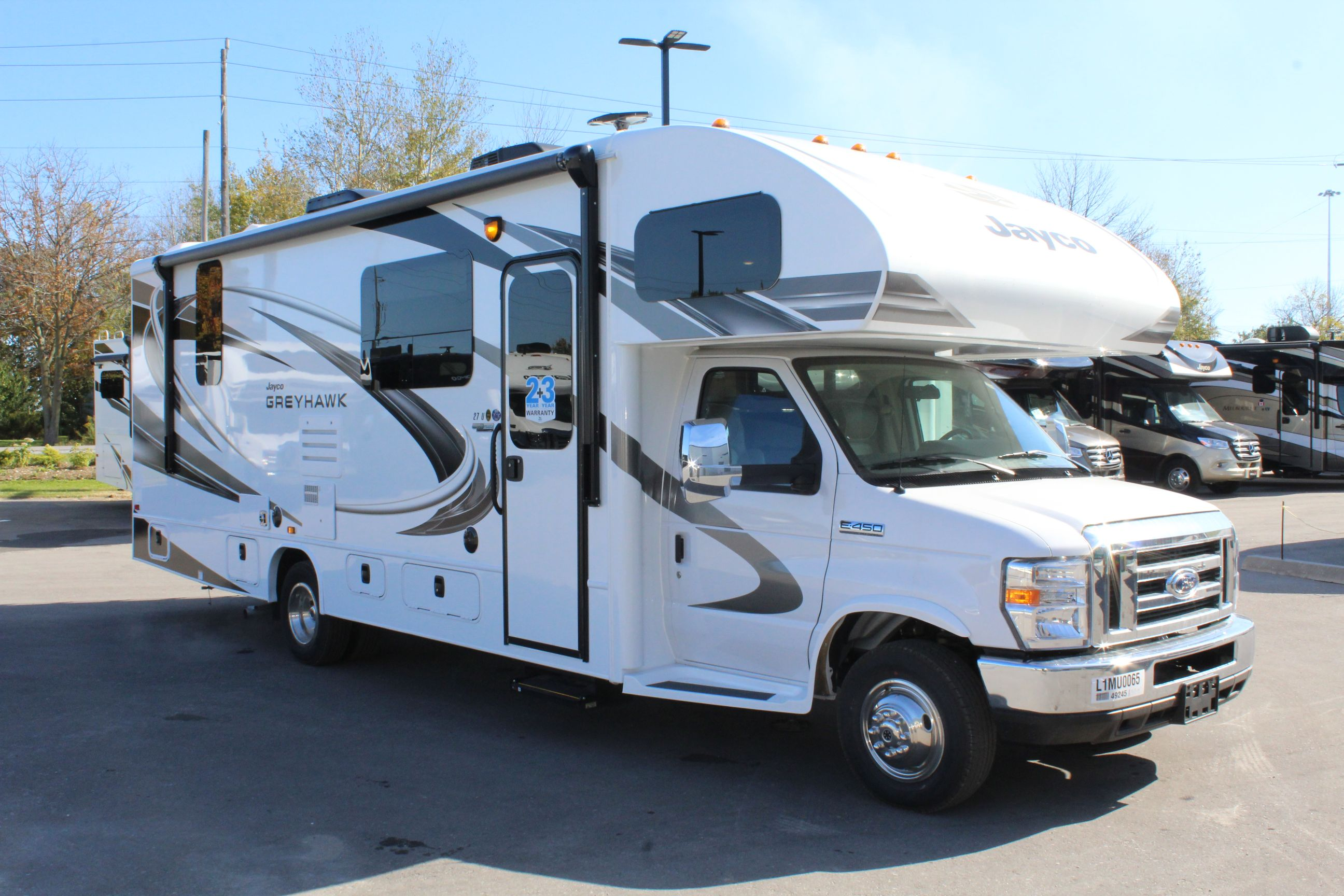 Front and Right sides of the Jayco Greyhawk 27U, with its 12V electric awning with LED lights, Remote-control, heated side-view mirrors, and Backup and side-view cameras/monitor.