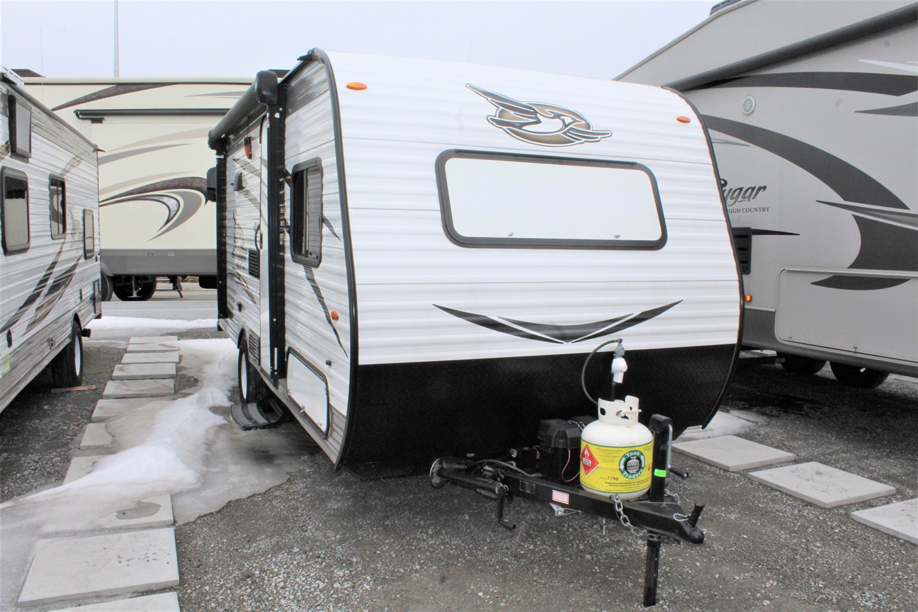 Front and Right exterior sides of the Jayco Jay Flight 174BH, with its 10' Power awning with LED light and integrated speakers, and a 20-pound propane bottle.