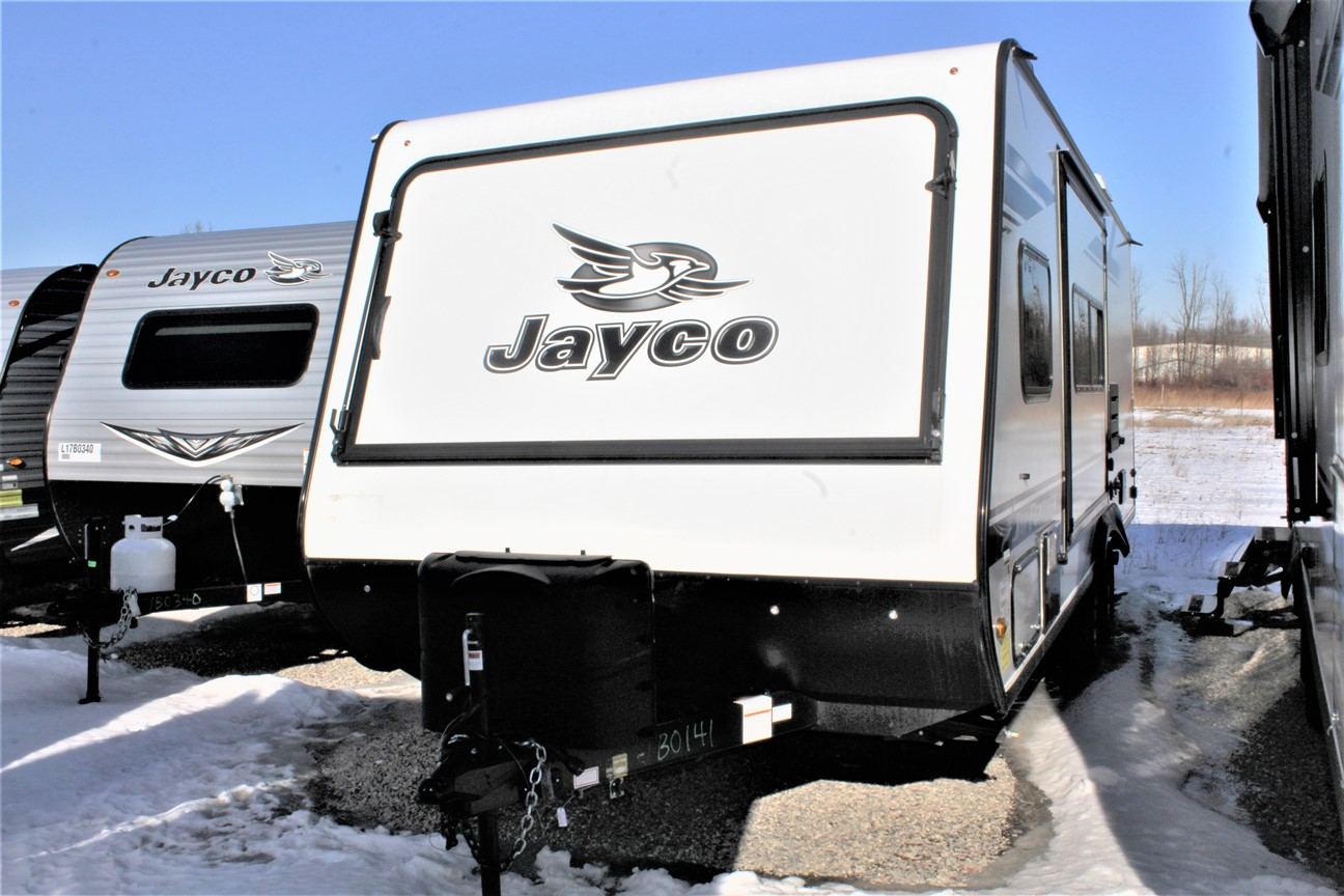 The front and left side of the Jayco Jay Feather X23B, with its double seals, barrier sponges, and U-channel drip spouts on its Slideouts, and its 2 20 lb. propane bottles with auto regulator.
