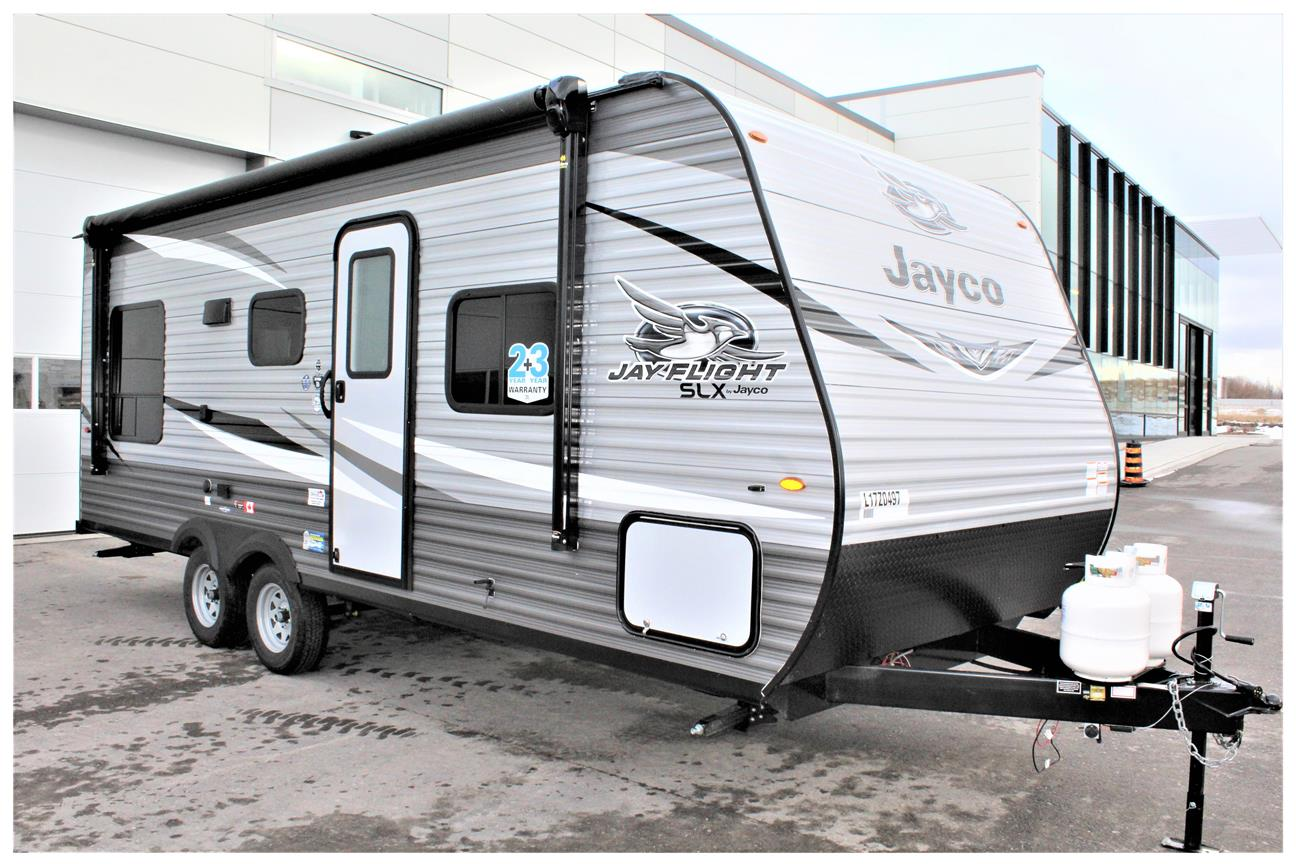 Front and rear of the Jayco Jay Flight SLX 212QB, 2 propane tanks are sitting on the tongue of the trailer the 16' awning.
