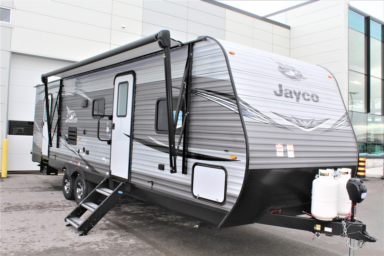 Front and Right exterior of the Jayco Jay Flight 28BHBE, the stairs leading into the trailer out with the awning slightly opened.