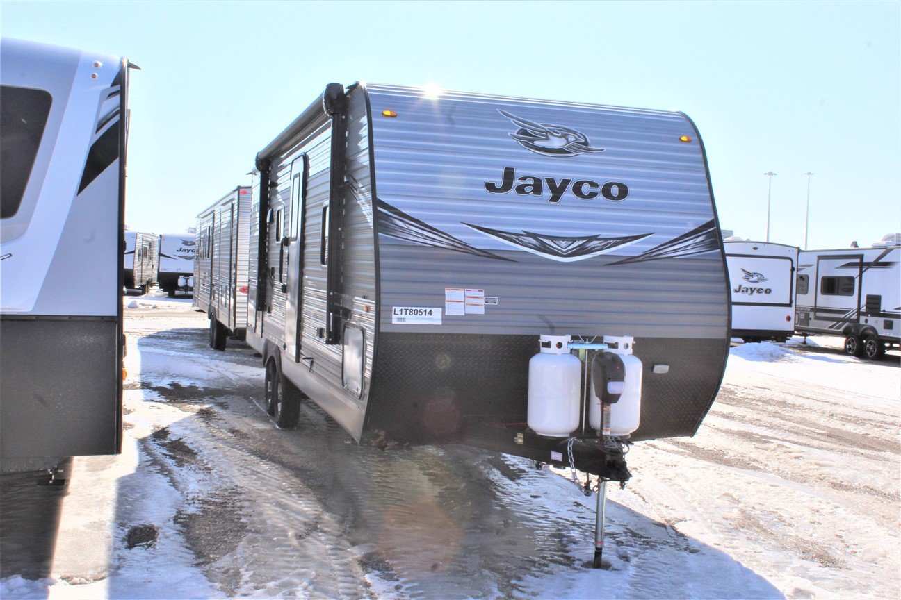 Front and Right Exterior Sides outside the Jayco Jay Flight 24RBS, with its 15' Power awning with speakers and LED lights, and 2 30 lb. propane bottles with cover,