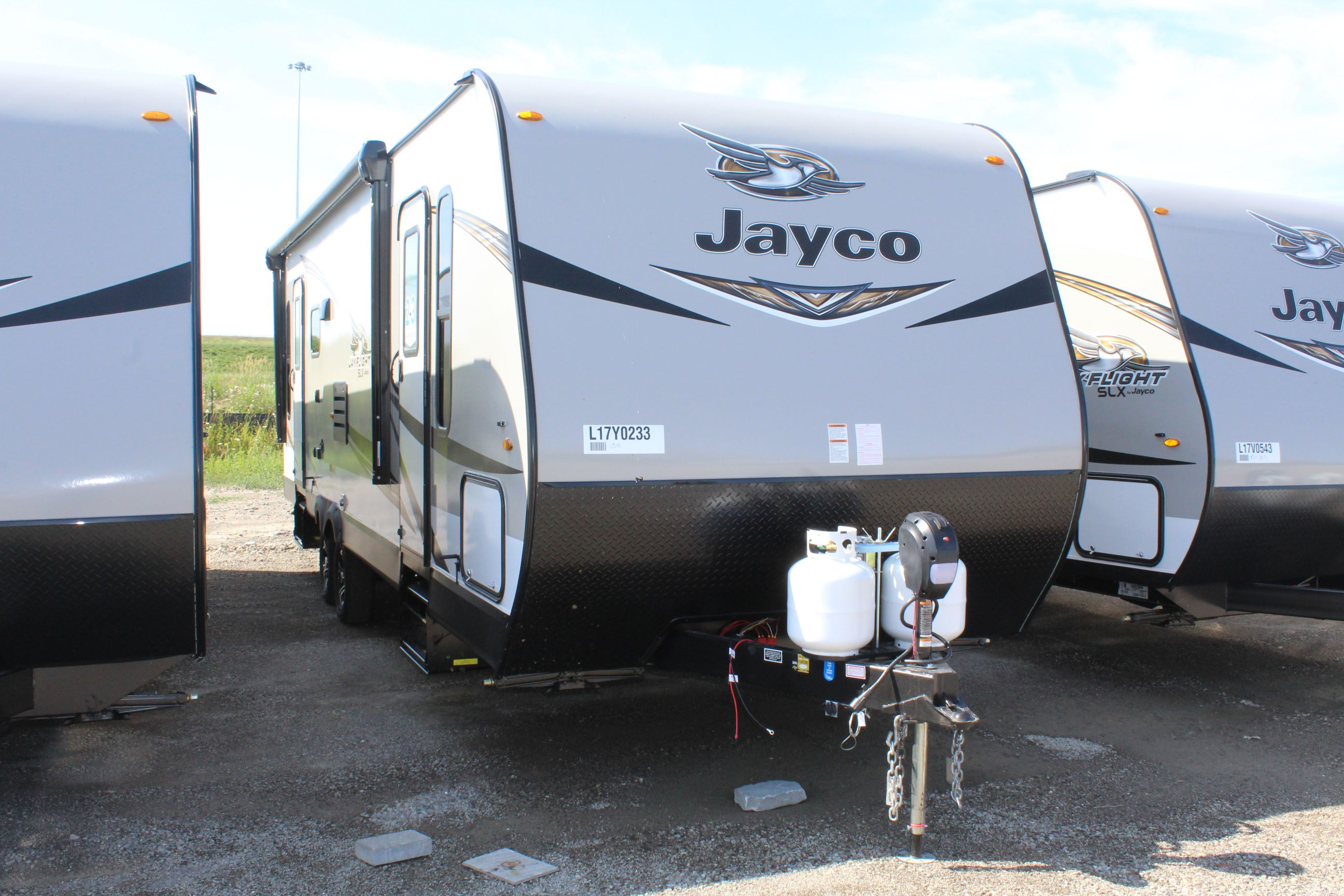 The Front and right side of the Jay Flight SLX 265RLS, with its 18' Power Awning with LED Lights & Speakers.
